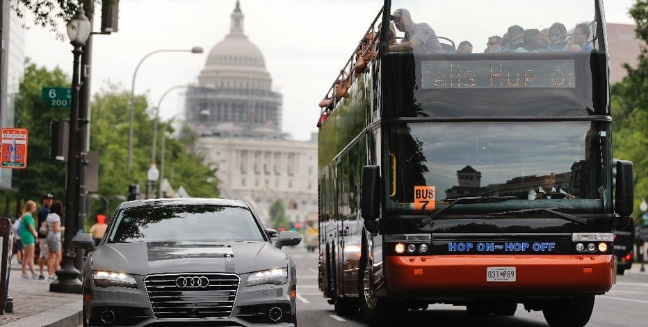 In this July 15, 2016, photo, a double decker tour bus drives by an Audi self driving vehicle parked on Pennsylvania Avenue, near the Capitol in Washington. The federal government should be in charge of regulating self-driving cars rather than states since the vehicles are essentially controlled by software, not people, Obama administration officials said Sept. 19 as they laid out the broad outlines of their plans to help get the transformational technology safely onto the nation's roadways. (AP Photo/Pablo Martinez Monsivais)
