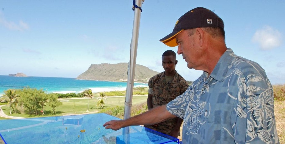 In this July 26, 2016 photo, Patrick Cross, specialist at the Hawaii Natural Energy Institute at the University of Hawaii at Manoa, shows a model of a wave energy machine called the Lifesaver, a donut-shaped device that converts the motion of waves into electricity, in Kaneohe Bay on Oahu in Hawaii. The cables in the middle move up and down with the waves, turning the wheels of generators in the donut-shaped Lifesaver device, which is deployed at the Navy's Wave Energy Test Site at the Marine Corps base in Kaneohe Bay. By some estimates, the ocean's endless motion packs enough power to meet a quarter of America's energy needs and dramatically reduce the nation's reliance on oil, gas and coal. But wave energy technology lags well behind wind and solar power. (AP Photo/Cathy Bussewitz)