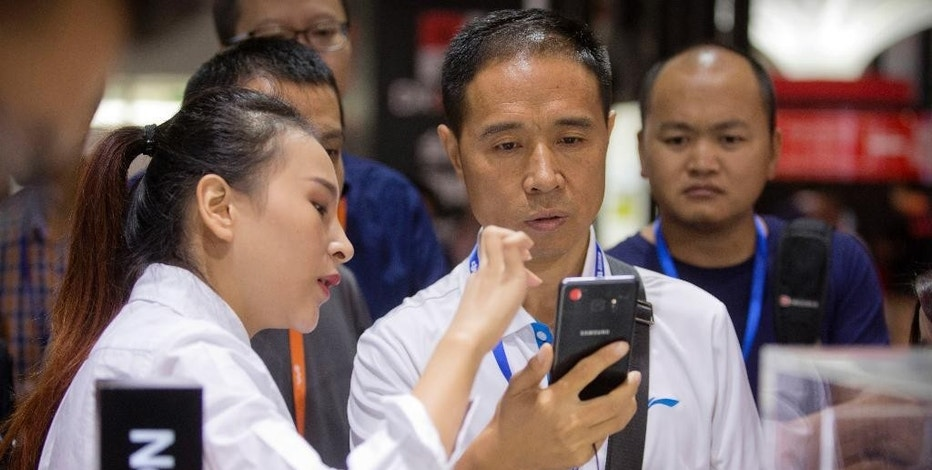 An assistant demonstrates the Galaxy Note 7 smartphone to a visitor at a Samsung Electronics display booth during an electronics expo in Beijing, Wednesday, Sept. 21, 2016. Samsung Electronics says its smartphones sold in China don't suffer the same problems as units that caught fire in the United States but Chinese customers complain the company is doing too little to reassure owners their handsets are safe. (AP Photo/Mark Schiefelbein)