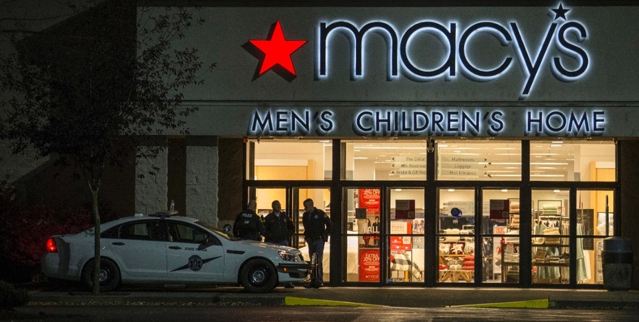 Law enforcement officers stand outside to the entrance of Macy's at the Cascade Mall where several people were shot and killed Friday Sept. 23, 2016 in Burlington, Wash. Police searched Saturday for a gunman who opened fire in the makeup department of a Macy's store at the mall north of Seattle, killing several females, before fleeing toward an interstate on foot, authorities said. (AP Photo/Stephen Brashear)