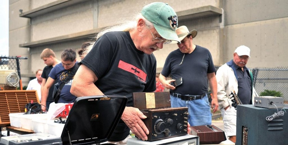 In this Sept. 18, 2016, photo, vendor Chuck Ochs shows a 1921 Crosley Model 51 radio, priced at $100, at MIT's Radio Society flea market on the campus of the Massachusetts Institute of Technology in Cambridge, Mass. Every third Sunday, MIT's Radio Society hosts a parking-lot flea market that's part yard sale and part curio museum from the world of electronics. Vendors come to hawk radio equipment, but also vintage Macintosh computers, castaway musical instruments, baubles of all kinds and the occasional space capsule. (AP Photo/Collin Binkley)