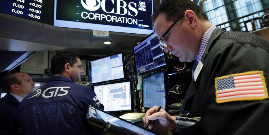 FILE - In this Wednesday, May 4, 2016, file photo, trader Edward Curran, right, works near the post that handles CBS Corp. on the floor of the New York Stock Exchange. On Thursday, Sept. 29, 2016, National Amusements, the company that controls CBS and Viacom, announced it wants the two media companies to combine again, more than a decade after they went their separate ways. CBS Corp. produces TV shows and owns its namesake network. Viacom Inc. owns cable channels MTV, Nickelodeon and VH1. (AP Photo/Richard Drew, File)