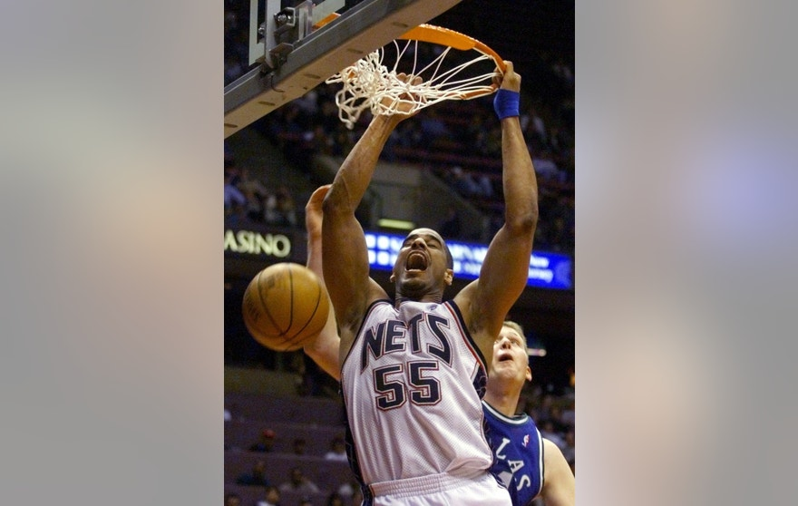 New Jersey Nets center Jayson Williams (55) stuffs the ball in front of Dallas Mavericks center Shawn Bradley in the fourth period of their NBA game, March 17 at the Meadowlands Arena in East Rutherford.