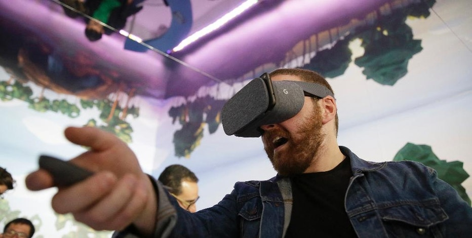 Dan Howley tries out the Google Daydream View virtual-reality headset and controller following a product event, Tuesday, Oct. 4, 2016, in San Francisco. Daydream View will differ from other headsets, like Samsung's Gear VR, in having a companion motion controller and compatibility with a wide range of phones, including Google's new Pixel phones. (AP Photo/Eric Risberg)