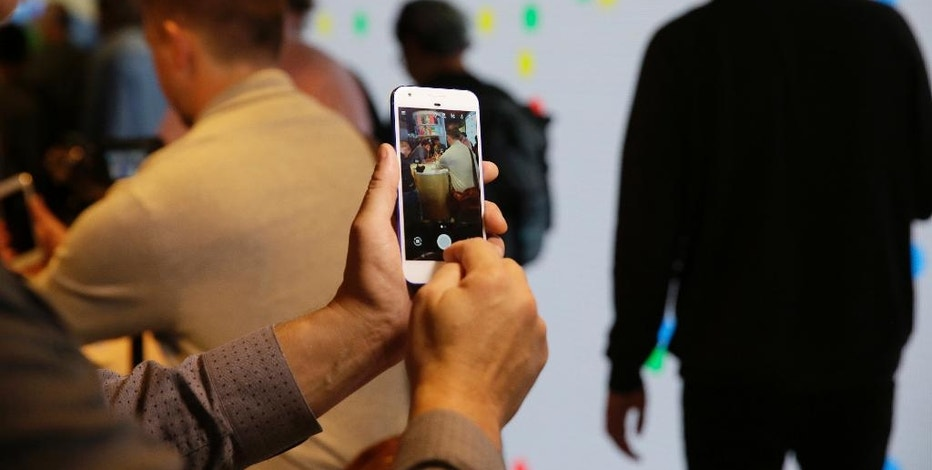 A reporter looks over the new Google Pixel phone following a product event, Tuesday, Oct. 4, 2016, in San Francisco. The new phones represent a push by Google to sell its own consumer devices, instead of largely just supplying software for other manufacturers. (AP Photo/Eric Risberg)
