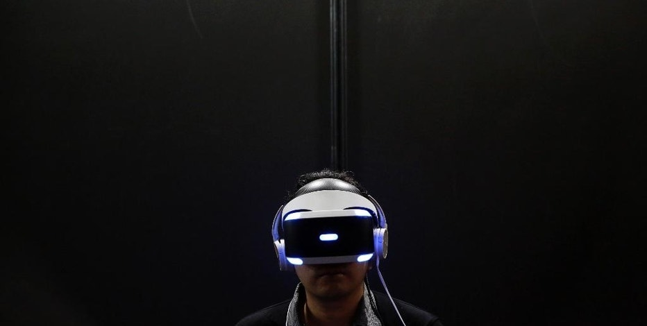 FILE - In this Sept. 15, 2016, file photo, a visitor tries out a PlayStation VR headgear device at the Tokyo Game Show in Makuhari, near Tokyo. Unlike the Oculus Rift and HTC Vive, PlayStation VR works in unison with a PlayStation 4 console instead of a high-end PC. It's also cheaper, more comfortable and will be the most convenient option for VR seekers when it's released Oct. 13. (AP Photo/Eugene Hoshiko, File)
