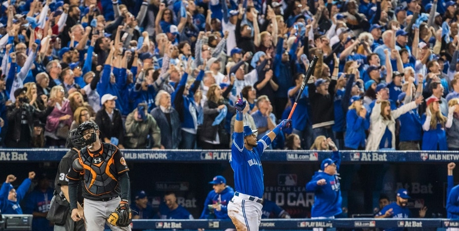 Toronto Blue Jays' Edwin Encarnacion raises his arms after hitting a walk-off three-run home run as the Baltimore Orioles catcher looks on during the 11th inning of an American League wild-card baseball game in Toronto, Tuesday, Oct. 4, 2016.