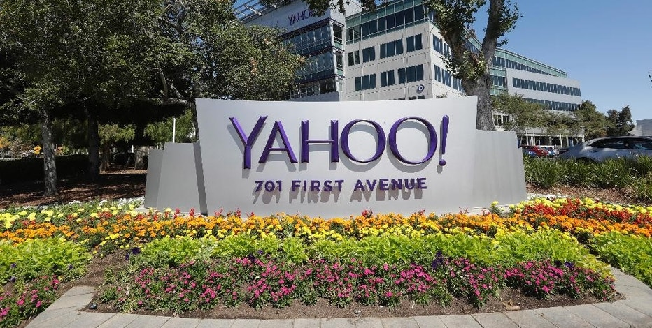 """In this Tuesday, July 19, 2016, photo, flowers bloom in front of a Yahoo sign at the company's headquarters in Sunnyvale, Calif. Yahoo responded again on Wednesday, Oct. 5, 2016, to a report that it scanned incoming email to hundreds of millions of accounts for the U.S government. In a carefully worded statement that stops short of a denial, the company said a Tuesday Reuters report is """"misleading,"""" saying that """"the mail scanning described in the article does not exist on our systems."""" (AP Photo/Marcio Jose Sanchez)"""