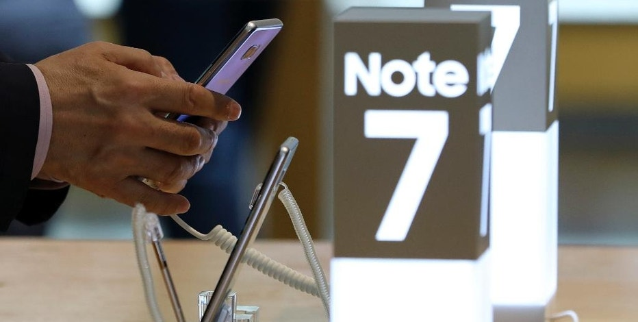 In this photo taken on Wednesday, Oct. 5, 2016, a man touches the Samsung Electronics Galaxy Note 7 smartphone at its shop in Seoul, South Korea. Samsung Electronics Co. estimated its profit rose more than expected in the July-September quarter despite the unprecedented recall of its flagship smartphones. (AP Photo/Lee Jin-man)