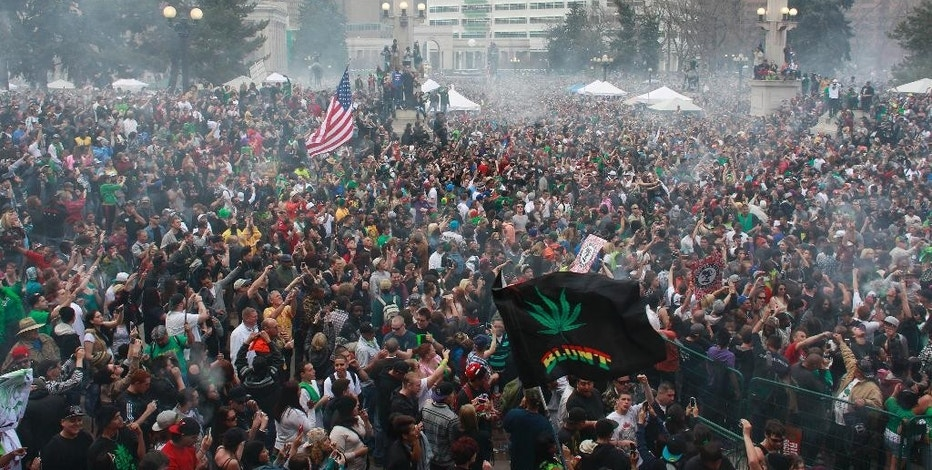 FILE - In this April 20, 2013 file photo, members of a crowd numbering tens of thousands smoke marijuana at the Denver 4/20 pro-marijuana rally at Civic Center Park in Denver. Denver police have said they would potentially use social media tracking software like Geofeedia to monitor the annual gathering. Increasingly common tools that allow police to conduct real-time social media surveillance during protests are drawing criticism from civil liberties advocates, who oppose the way some departments have quietly unrolled the technology without community input and little public explanation. (AP Photo/Brennan Linsley, File)