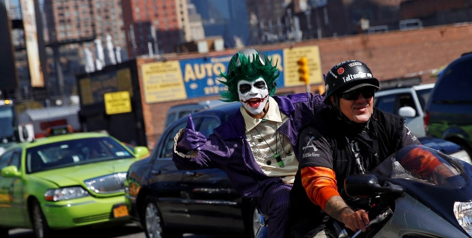 A man dressed in costume gives the thumbs up while riding on a motorcycle enroute to the New York Comic Con with other commuters in New York, U.S., October 6, 2016. REUTERS/Shannon Stapleton - RTSR2WE