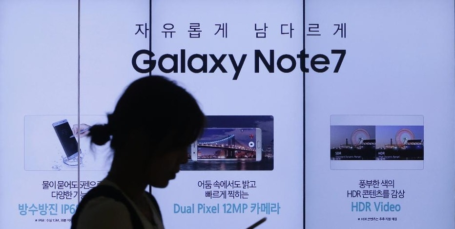 "FILE - In this Friday, Sept. 2, 2016, file photo, a woman walks by an advertisement of the Samsung Electronics Galaxy Note 7 smartphone at the company's showroom in Seoul, South Korea. Samsung is asking owners of its fire-prone Galaxy Note 7 to do something crazy: ""power down and stop using the device."" This is all but unthinkable in an age where smartphones have become an extra limb, the last thing we look at before falling asleep and the first thing we grab in the morning, not to mention throughout the day. (AP Photo/Ahn Young-joon, File)"