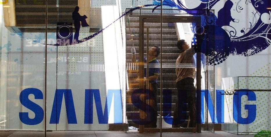 Workers clean a window at Samsung Electronics shop in Seoul, South Korea, Wednesday, Oct. 12, 2016. The fiasco of Samsung's fire-prone Galaxy Note 7 smartphones - and Samsung's stumbling response to the problem - has left consumers from Shanghai to New York reconsidering how they feel about the South Korean tech giant and its products. (AP Photo/Ahn Young-joon)