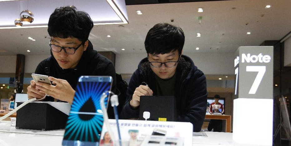 """FILE - In this Monday, Oct. 10, 2016, file photo, South Korean high school students try out Samsung Electronics Galaxy Note 7 smartphones at the company's shop in Seoul in Seoul, South Korea. Samsung is asking owners of its fire-prone Galaxy Note 7 to do something crazy: """"power down and stop using the device."""" This is all but unthinkable in an age where smartphones have become an extra limb, the last thing we look at before falling asleep and the first thing we grab in the morning, not to mention throughout the day. (AP Photo/Ahn Young-joon, File)"""