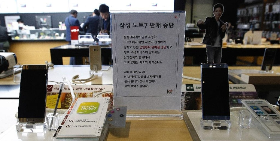 """Powered-off Samsung Electronics Galaxy Note 7 smartphones are displayed at a mobile phone shop in Seoul, South Korea, Tuesday, Oct. 11, 2016. Samsung Electronics said Tuesday that it is ending the Galaxy Note 7 smartphone production permanently, a day after it halted global sales of the star-crossed devices. The letters on the sign read """"We halt selling Samsung Electronics Galaxy Note 7 smartphones."""" (AP Photo/Ahn Young-joon)"""