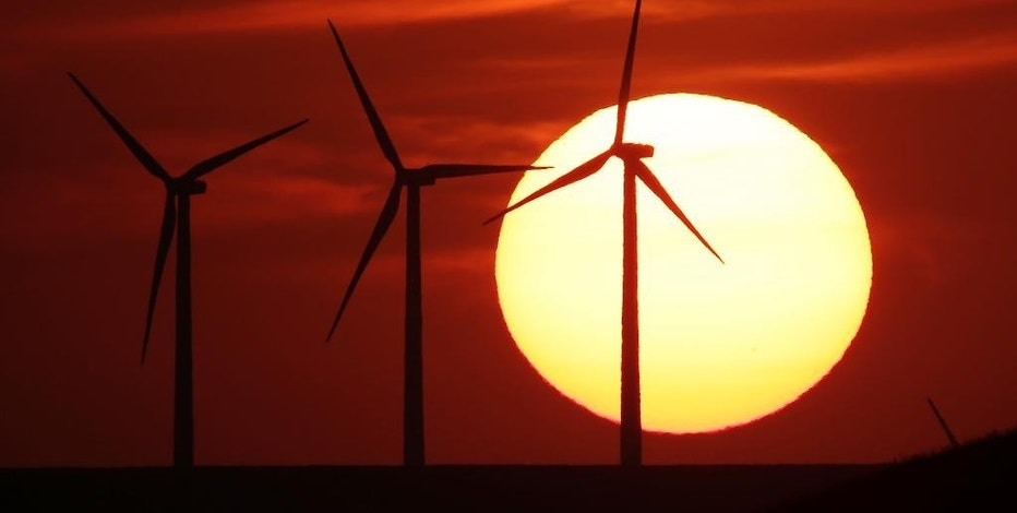 FILE - In this Aug. 23, 2013 file photo, wind turbines are silhouetted by the setting sun as they produce electricity near Beaumont, Kan. Energy independence has been a goal of every president since Richard Nixon. Hillary Clinton and Donald Trump have very different ways to achieve it. How energy is produced and where it comes from affect jobs, the economy and the environment. (AP Photo/Charlie Riedel, File)