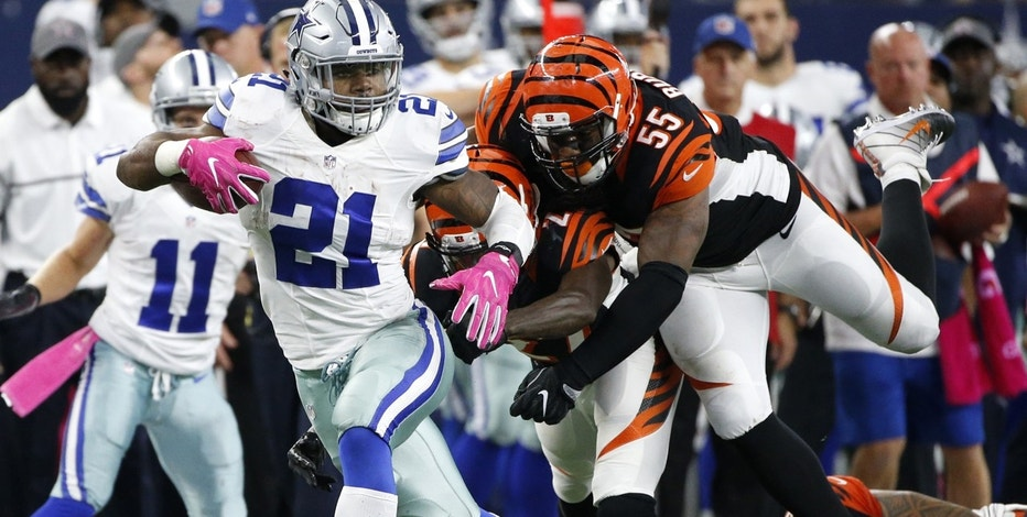 Dallas Cowboys' Ezekiel Elliott (21) evades pressure from Cincinnati Bengals' Dre Kirkpatrick (27) and Vontaze Burfict (55) in as Elliott carries the ball in the second half of an NFL football game, Sunday, Oct. 9, 2016, in Arlington, Texas.