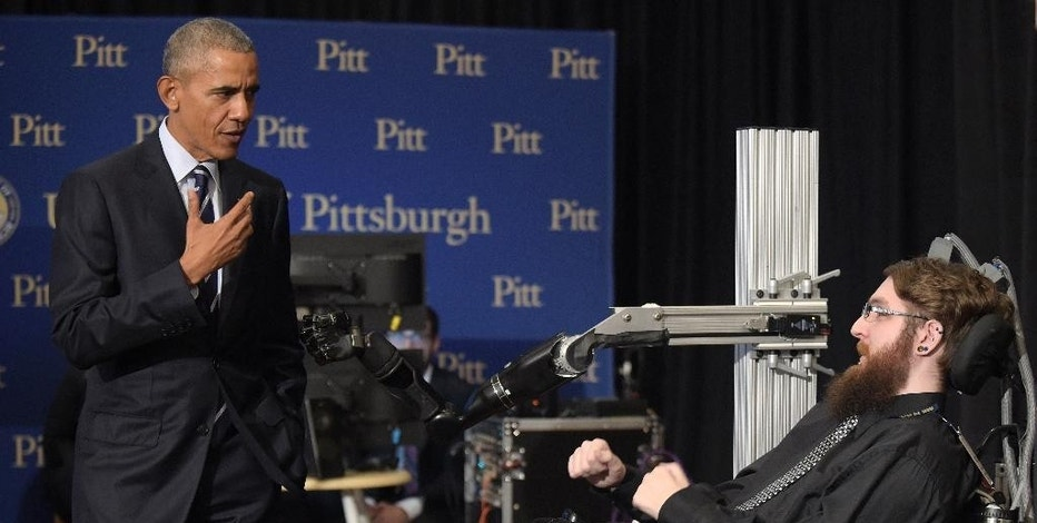 President Barack Obama talks with Nathan Copeland, right, during a tour of innovation projects at the White House Frontiers Conference at University of Pittsburgh in Pittsburgh, Thursday, Oct. 13, 2016. Copeland demonstrates how he can control a robotic arm and feel when the robotic hand is touched. (AP Photo/Susan Walsh)
