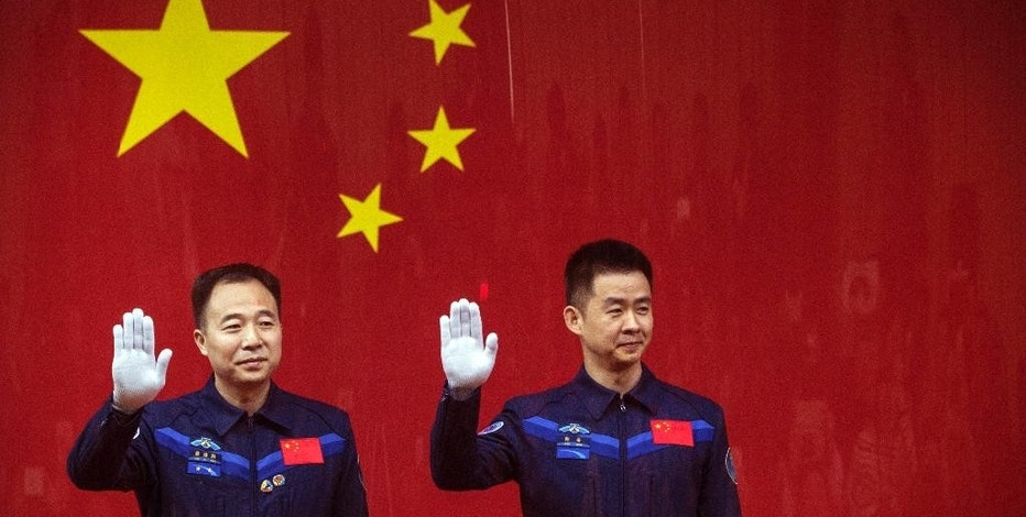 Chinese astronauts Jing Haipeng, left, and Chen Dong, right, wave from behind a glass enclosure during a presser at the Jiuquan Satellite Launch Center in northwest China Sunday Oct. 16, 2016. Chinese officials unveiled plans for Monday's launch of the country's latest space mission in which the two astronauts will be blasted into space and will dock with an orbiting space lab. (Chinatopix Via AP)