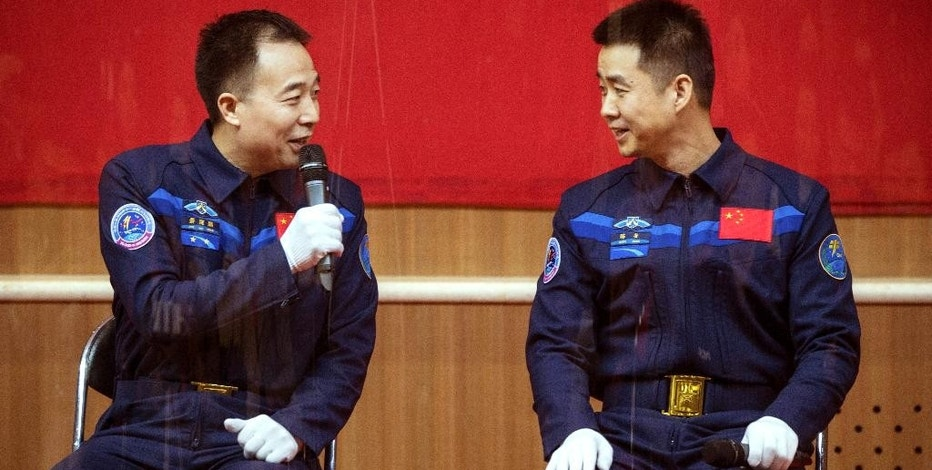 Chinese astronauts Jing Haipeng, left, and Chen Dong, right, chat behind a glass enclosure during a presser at the Jiuquan Satellite Launch Center in northwest China Sunday Oct. 16, 2016. Chinese officials unveiled plans for Monday's launch of the country's latest space mission in which the two astronauts will be blasted into space and will dock with an orbiting space lab. (Chinatopix Via AP)