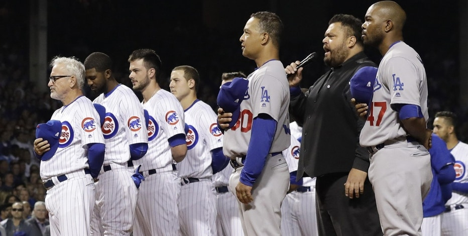 Chicago Cubs and Los Angeles Dodgers players observes the national anthem before Game 1 of the National League baseball championship series Saturday, Oct. 15, 2016, in Chicago.