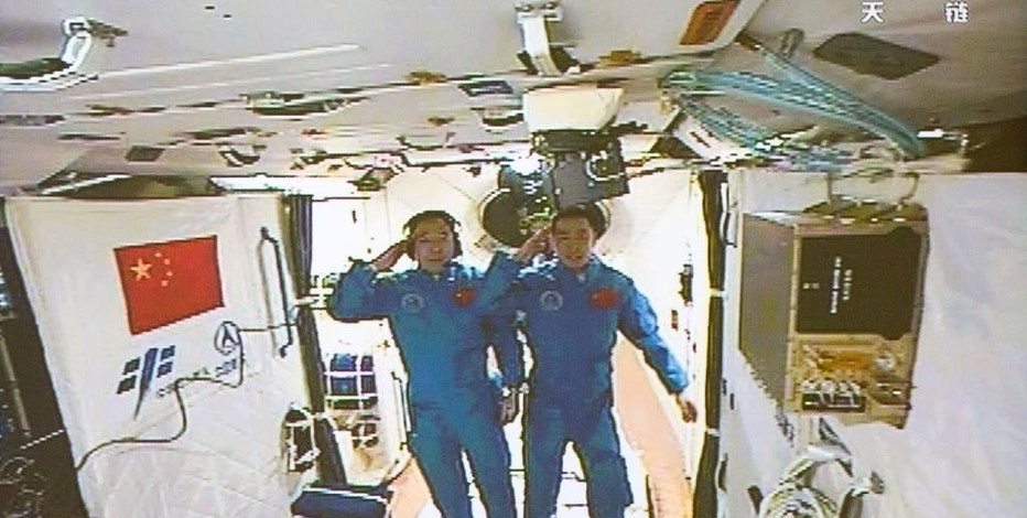 """In this image taken off the screen at the Beijing Aerospace Control Center on Wednesday, Oct. 19, 2016 and released by Xinhua News Agency, two Chinese astronauts Jing Haipeng, left and Chen Dong salute in the space lab Tiangong 2. China says a pair of astronauts aboard have entered the country's orbiting space station for a month-long stay. Chinese character on bottom left reads """"Inside Tiangong."""" (Ju Zhenhua/Xinhua via AP)"""