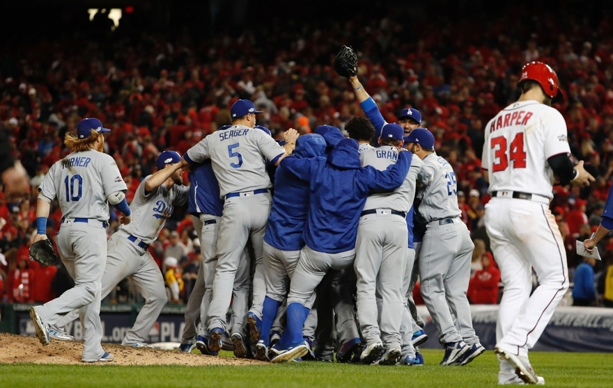 As Washington Nationals' Bryce Harper (34) walks from the field, the Los Angeles Dodgers celebrate a 4-3 win in Game 5 of a baseball National League Division Series, at Nationals Park early Friday, Oct. 14, 2016, in Washington.