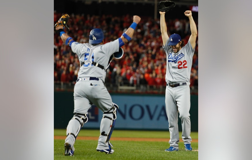 Los Angeles Dodgers pitcher Clayton Kershaw (22) and catcher Carlos Ruiz celebrate after Washington Nationals' Wilmer Difo struck out to end Game 5 of baseball's National League Division Series at Nationals Park early Friday, Oct. 14, 2016, in Washington. The Dodgers won 4-3.