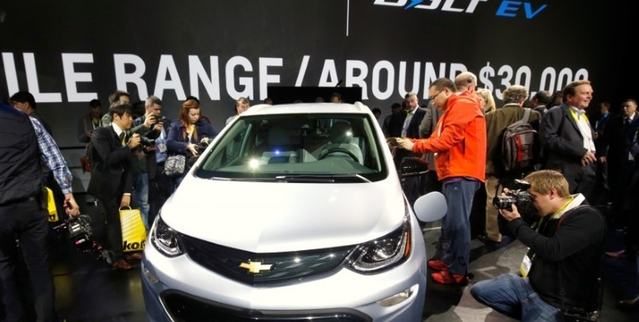 Journalists look over the 2017 Chevrolet Bolt EV after it is unveiled during a General Motors keynote address at the 2016 CES trade show in Las Vegas, Nevada January 6, 2016. REUTERS/Steve Marcus