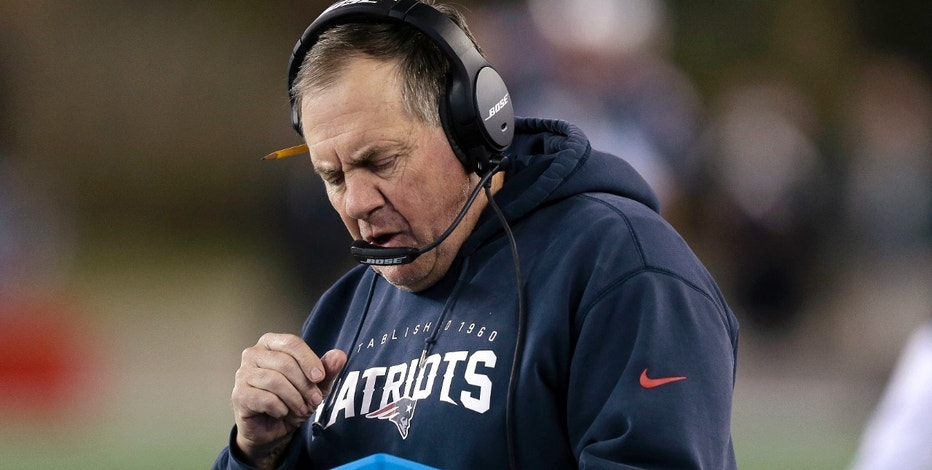 FILE - In this Dec. 6, 2015, file photo, New England Patriots head coach Bill Belichick studies a tablet device along the sideline during the first half of an NFL football game against the Philadelphia Eagles in Foxborough, Mass. Belichick said Tuesday, Oct. 18, 2016, that he's through using the sideline tablets, saying there isn't enough consistency in the performance of the devices. (AP Photo/Charles Krupa, File)