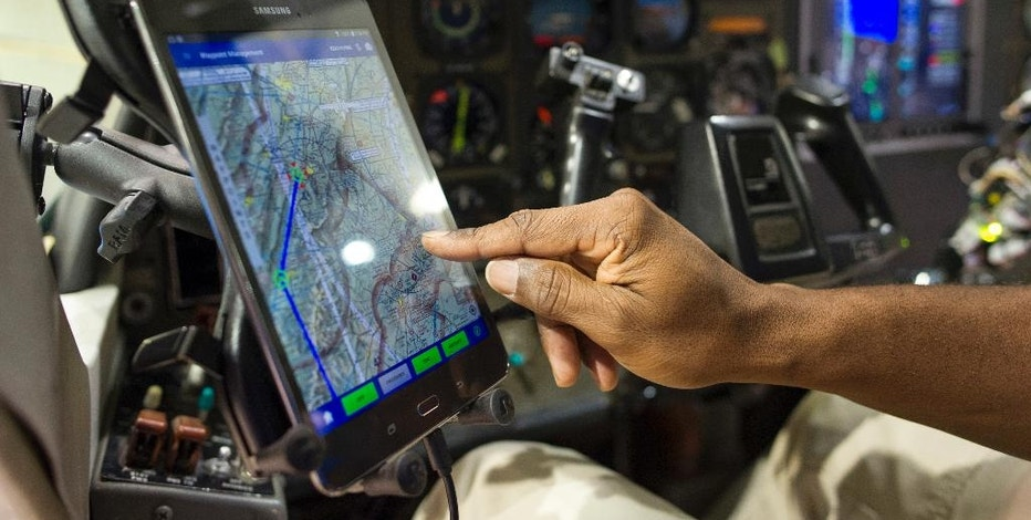 A pilot demonstrates how a tablet inflight controls the Aurora Flight Sciences' Aircrew Labor In-Cockpit Automantion System (ALIAS), which is mounted in a Cessena Caravan aircraft at Manassas Airport in Manassas, Va., Monday, Oct. 17, 2016. Government and industry are working together on a robot-like autopilot system that could eliminate the need for a second human pilot in the cockpit. (AP Photo/Cliff Owen)