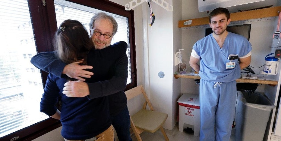 Stephen DeMont, center, embraces Madeline Dahl as Zach Forcade looks on at the University of Washington Medical Center Wednesday, Oct. 19, 2016, in Seattle. When DeMont collapsed at a bus stop in front of the UW Medical Center days earlier on his morning commute, Dahl was one of 41 people within a 330-yard radius who happened to have a cell phone app alerting them to the emergency. Forcade, a medical student, witnessed the collapse and rushed over to begin chest compressions, as within moments Dahl, a cardiac nurse just getting off her shift in the hospital, was alerted by her phone and sprinted down the sidewalk, assisting until paramedics arrived. (AP Photo/Elaine Thompson)