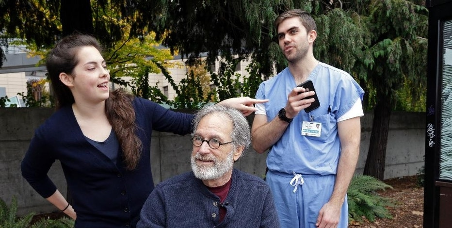 Madeline Dahl, left, looks on as Zach Forcade, right, pulls out his cell phone while Stephen DeMont sits with them while being interviewed at the University of Washington Medical Center Wednesday, Oct. 19, 2016, in Seattle. When DeMont collapsed at a bus stop in front of the UW Medical Center days earlier on his morning commute, Dahl was one of 41 people within a 330-yard radius who happened to have a cell phone app alerting them to the emergency. Forcade, a medical student, witnessed the collapse and rushed over to begin chest compressions, as within moments Dahl, a cardiac nurse just getting off her shift in the hospital, was alerted by her phone and sprinted down the sidewalk, assisting until paramedics arrived. (AP Photo/Elaine Thompson)