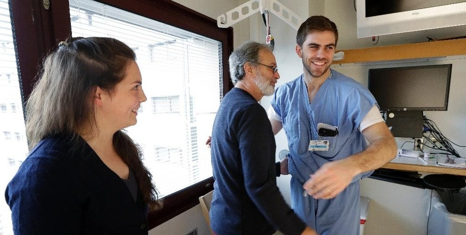 Stephen DeMont, center, gets a hug from medical student Zach Forcade, right, as nurse Madeline Dahl looks on as they visit DeMont Wednesday, Oct. 19, 2016 at the University of Washington Medical Center, in Seattle. When DeMont collapsed at a bus stop in front of the UW Medical Center days earlier on his morning commute, Dahl was one of 41 people within a 330-yard radius who happened to have a cell phone app alerting them to the emergency. Forcade witnessed the collapse and rushed over to begin chest compressions, as within moments Dahl, a cardiac nurse just getting off her shift in the hospital, was alerted by her phone and sprinted down the sidewalk, assisting until paramedics arrived. (AP Photo/Elaine Thompson)