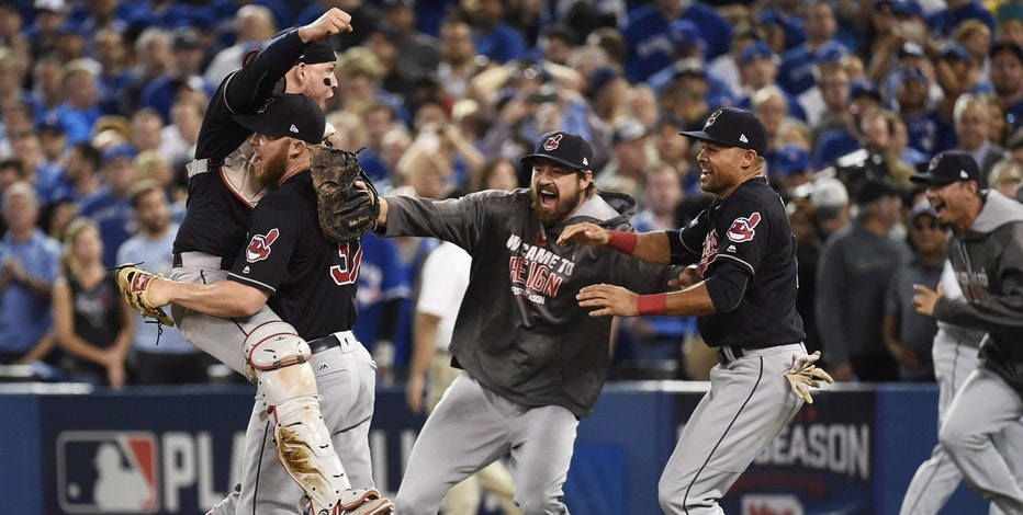 In this Wednesday, Oct. 19, 2016, file photo, Cleveland Indians relief pitcher Cody Allen (37), cather Roberto Perez (55) and teammates Andrew Miller and Coco Crisp celebrate the team's 3-0 victory over the Toronto Blue Jays during Game 5 of the baseball American League Championship Series, in Toronto. Four months after LeBron James and the Cavaliers ended the city's championship drought at 52 years by winning the NBA title, the Indians are back in the World Series for the first time since 1997.