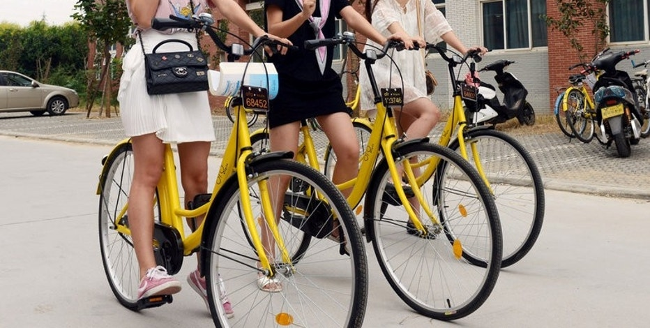 Students pose for pictures as they use ofo sharing bicycles at a campus in Zhengzhou, Henan province, China, September 6, 2016. China Daily/via REUTERS/File Photo