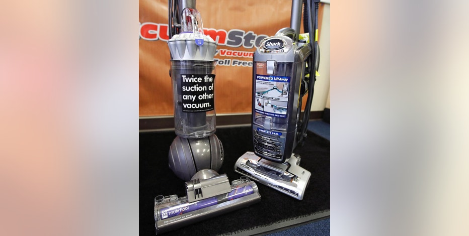 A Dyson, left, and SharkNinja upright vacuum cleaners are positioned together at the evacuumstore.com retail location in Braintree, Mass., Thursday, Oct. 20, 2016. Dyson and SharkNinja, fierce competitors in the U.S. vacuum cleaner market, have settled a bitter legal dispute. The two companies were to have duked it out in federal court over advertising campaigns in which each claimed their vacuums had the best suction or cleaned better. (AP Photo/Charles Krupa)