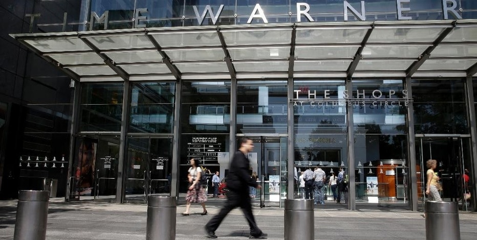 FILE - In this Tuesday, May 26, 2015 file photo, pedestrians walk by an entrance to the Time Warner Center in New York. On Saturday, Oct. 22, 2016, several reports citing unnamed sources said AT&T is in advanced talks to buy Time Warner, owner of the Warner Bros. movie studio as well as HBO and CNN. The giant phone company is said to be offering $80 billion or more, a massive deal that would shake up the media landscape. (AP Photo/Mary Altaffer)
