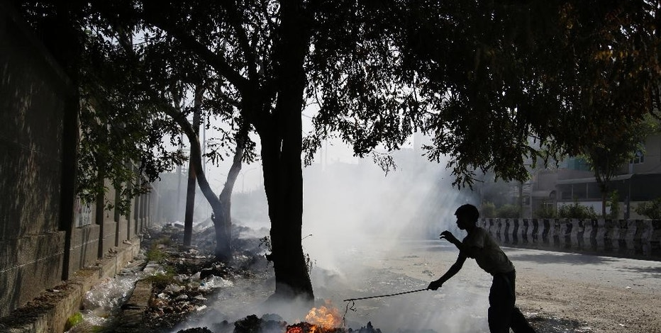 A young Indian ragpicker is silhouetted against smoke rising from the garbage burning on the roadside on the outskirts of New Delhi, India, Saturday, Oct. 22, 2016. The Indian capital, laboring under the label of being the world's most polluted city, is trying something new to help clean up its air. A smartphone application that allows citizens to report the presence of construction dust or the burning of leaves and garbage in public parks to authorities was launched Friday. (AP Photo/Altaf Qadri)