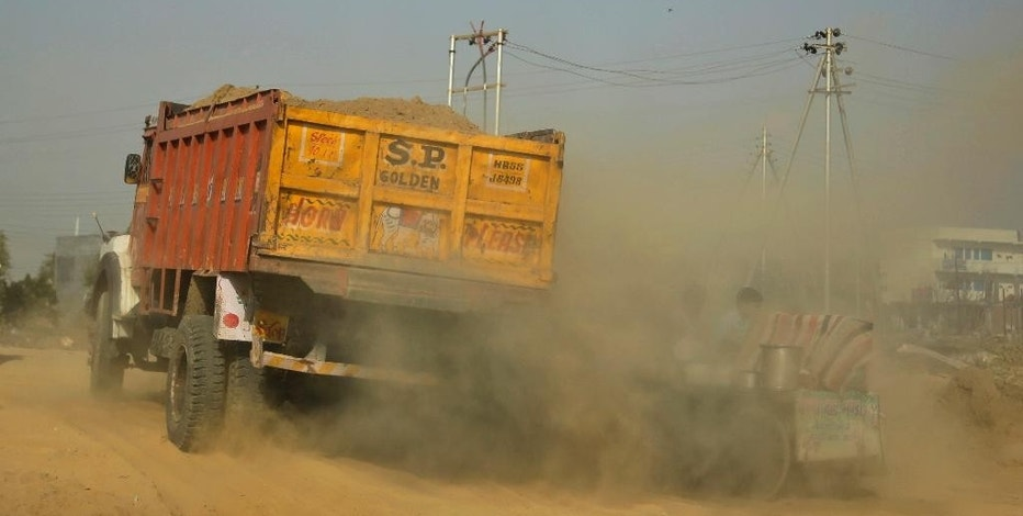 "Smoke emitted from a passing truck and dust engulfs a vendor on the outskirts of New Delhi, India, Saturday, Oct. 22, 2016. A smartphone application that allows citizens to report the presence of construction dust or the burning of leaves and garbage in public parks to authorities was launched Friday in the Indian capital. The ""Hawa Badlo,"" or ""Change the Air,"" app has two versions. One allows citizens to take pictures of likely pollutants. The other allows authorities to investigate and act on valid complaints. (AP Photo/Altaf Qadri)"