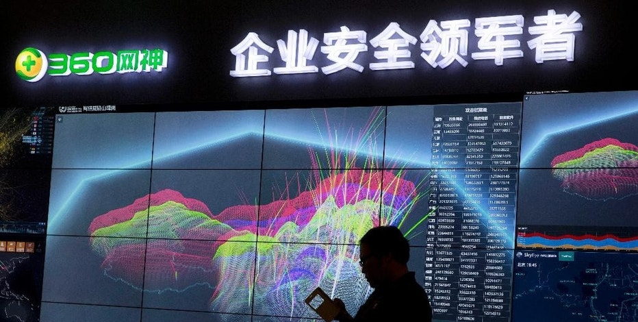FILE - In this Aug. 16, 2016 file photo, a worker is silhouetted against a computer display showing a live visualization of the online phishing and fraudulent phone calls across China during the 4th China Internet Security Conference (ISC) in Beijing. Chinese electronics maker Hangzhou Xiongmai Technology has issued a recall on Monday, Oct. 24, 2016, for millions of products sold in the U.S. following a devastating cyberattack, but has lashed out at critics who say its devices were at fault. (AP Photo/Ng Han Guan, File)