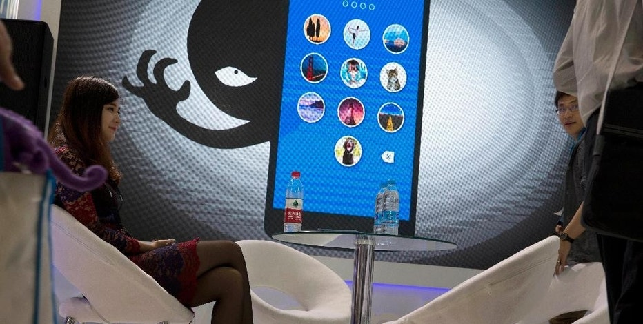 In this April 29, 2016, file photo, a woman sits near a display showing the dangers of hackers breaking into mobile devices during the Global Mobile Internet Conference in Beijing. Chinese electronics maker Hangzhou Xiongmai Technology has issued a recall on Monday, Oct 24, 2016, for millions of products sold in the U.S. following a devastating cyberattack, but has lashed out at critics who say its devices were at fault.  (AP Photo/Ng Han Guan, File)