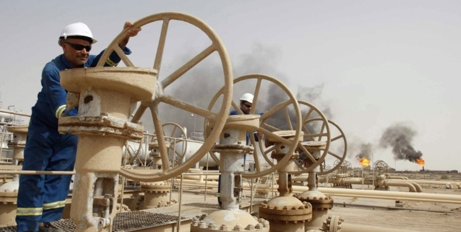 Workers adjust the valves of an oil pipe as smoke rises from burning excess gas (in the background) in Zubair oilfield in Basra, 420 km (260 miles) southeast of Baghdad May 23, 2011.   REUTERS/Atef Hassan