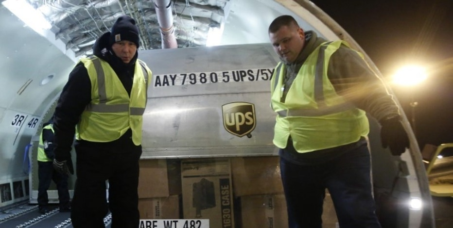 United Parcel Service (UPS) employees unload packages from the cargo of an airplane at the Regional Air Hub in Rockford, Illinois, December 9, 2014. Picture taken December 9, 2014. REUTERS/Jim Young