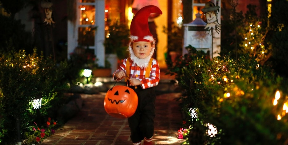 A boy collects candy as he goes trick-or-treating for Halloween in Santa Monica, California, October 31, 2012. REUTERS/Lucy Nicholson (UNITED STATES - Tags: SOCIETY) - RTR39UJS