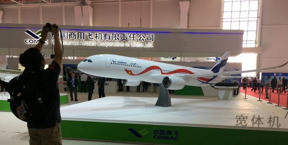 A man takes picture of the model of a widebody jet, which is planned to be developed by Commercial Aircraft Corporation of China (COMAC) and Russia's United Aircraft Corporation (UAC) at an air show, the China International Aviation and Aerospace Exhibition, in Zhuhai, Guangdong Province, China, November 2, 2016. REUTERS/Brenda Goh