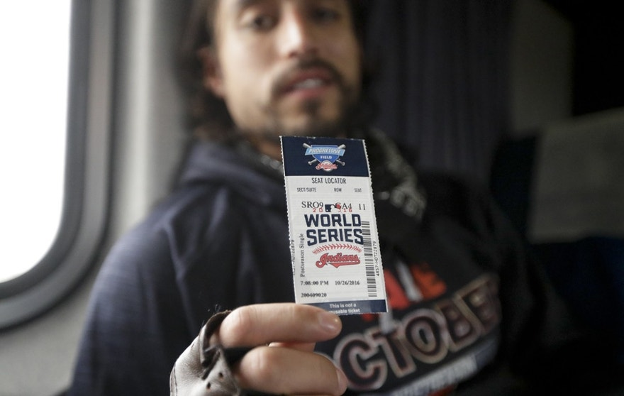 Salvador Cardenas, a 28-year-old dentist from Aurora, Illinois, shows off his ticket from Game 2 of the baseball's World Series between the Cleveland Indians and the Chicago Cubs in Cleveland, aboard the train to Chicago's Union Station, Thursday, Oct. 27, 2016.