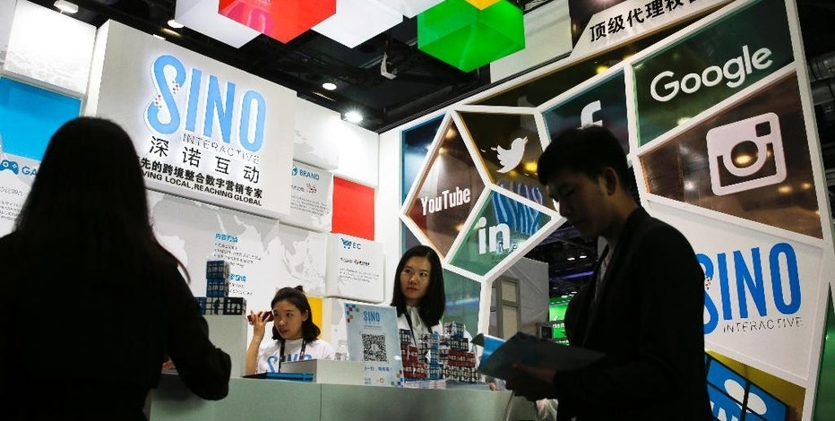 In this April 28, 2016 photo, a visitor browses a booklet at a social network company booth which enable people to connect global clients during the 2016 Global Mobile Internet Conference (GMIC) in Beijing. China's legislature has approved a cybersecurity law on Monday, Nov. 7, 2016 that human rights activists warn will tighten political controls and foreign companies say might isolate Chinese industries. (AP Photo/Andy Wong)