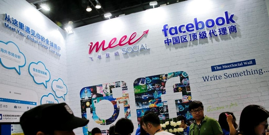 In this April 28, 2016 photo, visitors gather at a social network company booth which enable people to connect global clients during the 2016 Global Mobile Internet Conference (GMIC) in Beijing. China's legislature has approved a cybersecurity law on Monday, Nov. 7, 2016 that human rights activists warn will tighten political controls and foreign companies say might isolate Chinese industries. (AP Photo/Andy Wong)