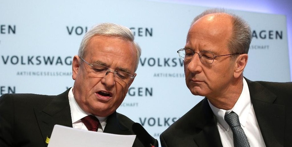 FILE - In this March 13, 2014 file photo then Volkswagen CEO Martin Winterkorn, left, and then CFO Hans Dieter Poetsch, right, talk prior to the company's annual press conference in Berlin, Germany. Volkswagen said in a statement Sunday, Nov. 6, 2016, that prosecutors have widened their investigation of the emissions scandal to include the chairman of the company's board of directors Poetsch. Prosecutors were already investigating former CEO Winterkorn and another unnamed executive over allegations they didn't inform investors soon enough. (AP Photo/Michael Sohn, file)